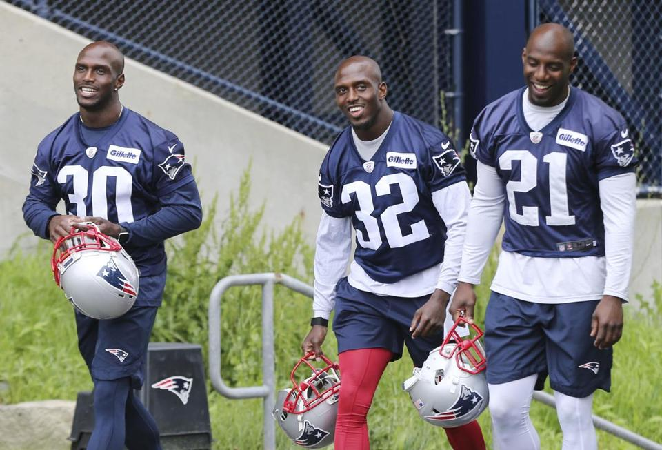 New England Patriots defensive backs Jason McCourty (30), Devin McCourty (32) and Duron Harmon (21) walk to an NFL football minicamp practice, Wednesday, June 6, 2018, in Foxborough, Mass. (AP Photo/Elise Amendola)