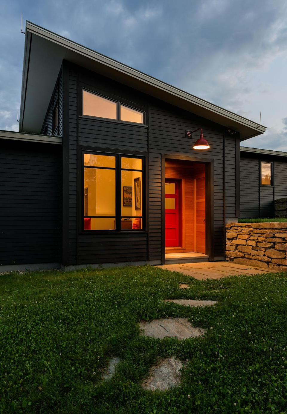 Below: Like the pergola, the front door is painted to match the Barn Light Electric Company sconce. The color, which references traditional New England barns, pops against the home's black clapboard siding.