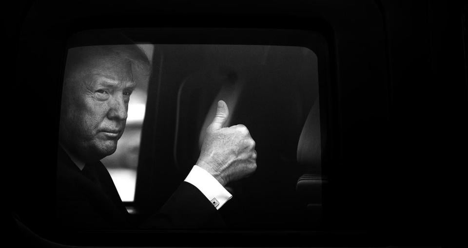 President Donald Trump gives a thumbs up from the presidential SUV.