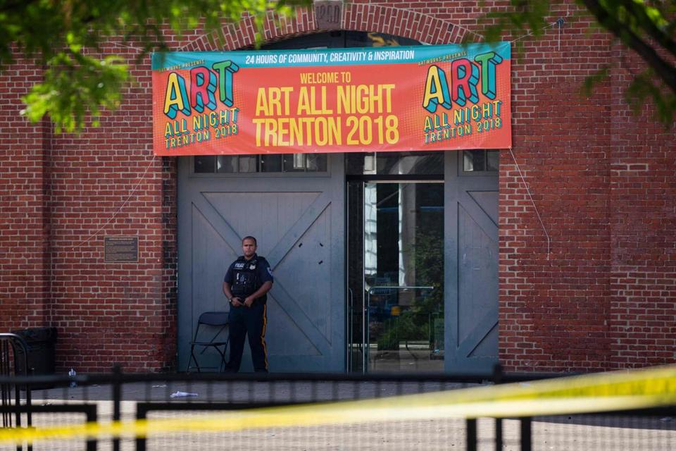 A Police officer stands in front as other officers inspect the crime scene at the Roebling Market on June 17, 2018, the morning after a shooting at an all-night art festival injured 20 people and left one suspect dead in Trenton, New Jersey. / AFP PHOTO / DOMINICK REUTERDOMINICK REUTER/AFP/Getty Images