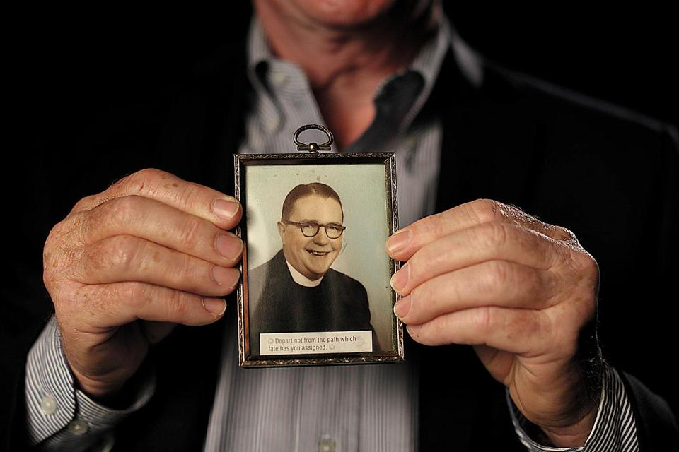 Jim Graham with a picture of the Rev. Thomas Sullivan, who he contends was his father.  Suzanne Kreiter/Globe staff)