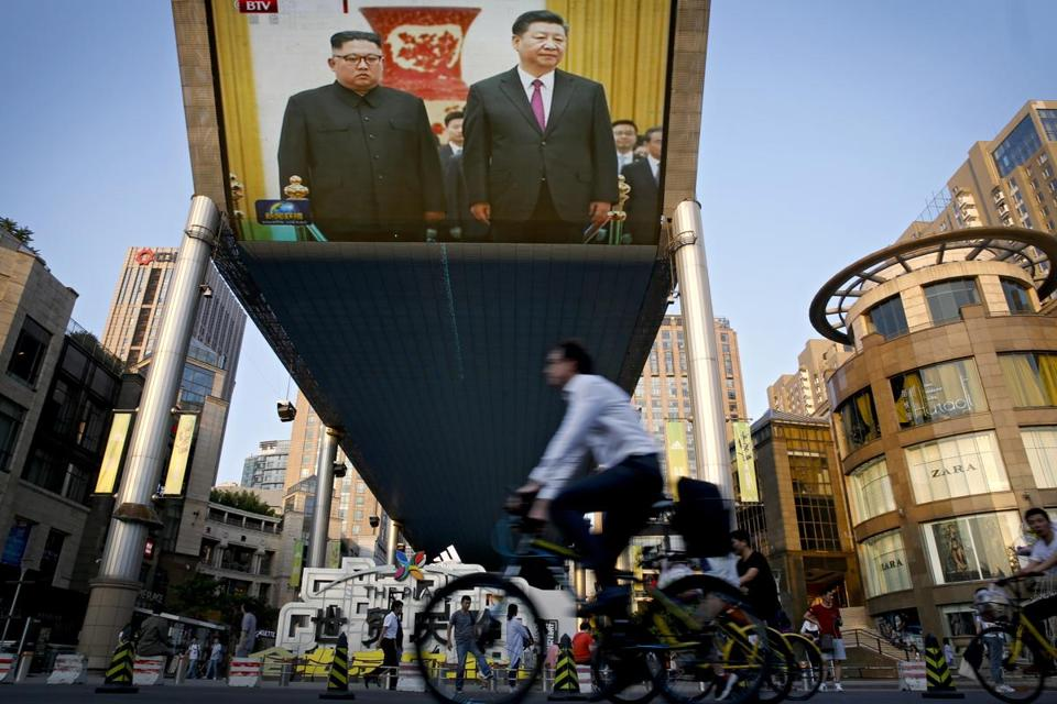 A giant TV screen showed North Korean leader Kim Jong Un and Chinese President Xi Jinping meeting on Tuesday.