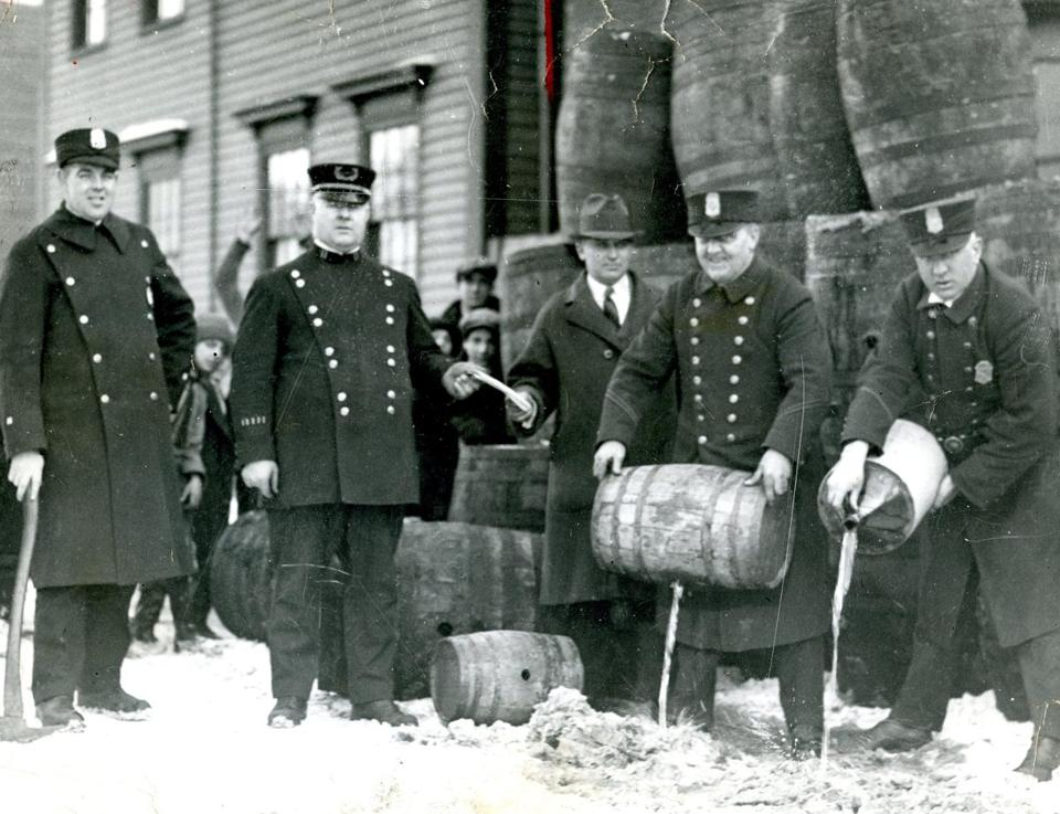 Undated / fromthearchive / Globe photo by Hugh E. O'Donnell / Cambridge Officer Patrick F. Ready has his ax in hand as the police liquor raiding party pours illicit liquor down an East Cambridge sewer. Others in the photo, L to R are Captain Timothy Leahy, an unidentifed prohibition agent, Officer Fred Collins and Officer Timothy Callahan.