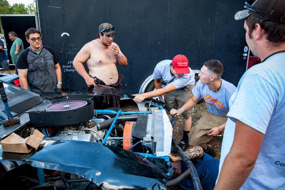 Driver Austin Erickson (shirtless) and his team make adjustments between races.