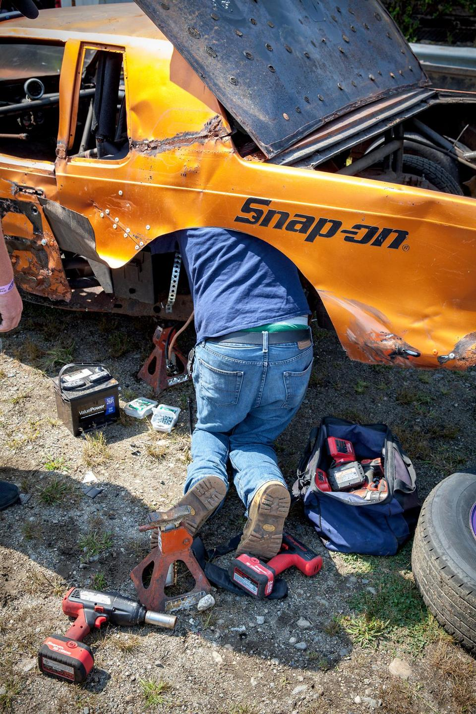 A mechanic at Hudson Speedway works on getting one car ready.