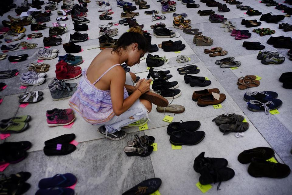 A woman places one of the hundreds of shoes in memory of those killed by Hurricane Maria in front of the Puerto Rico Capitol, in San Juan, Friday, June 1, 2018. Puerto Rico's Institute of Statistics announced that it has sued the U.S. territory's health department and demographic registry seeking to obtain data on the number of deaths following Hurricane Maria as a growing number of critics accuse the government of lacking transparency. (AP Photo/Ramon Espinosa)