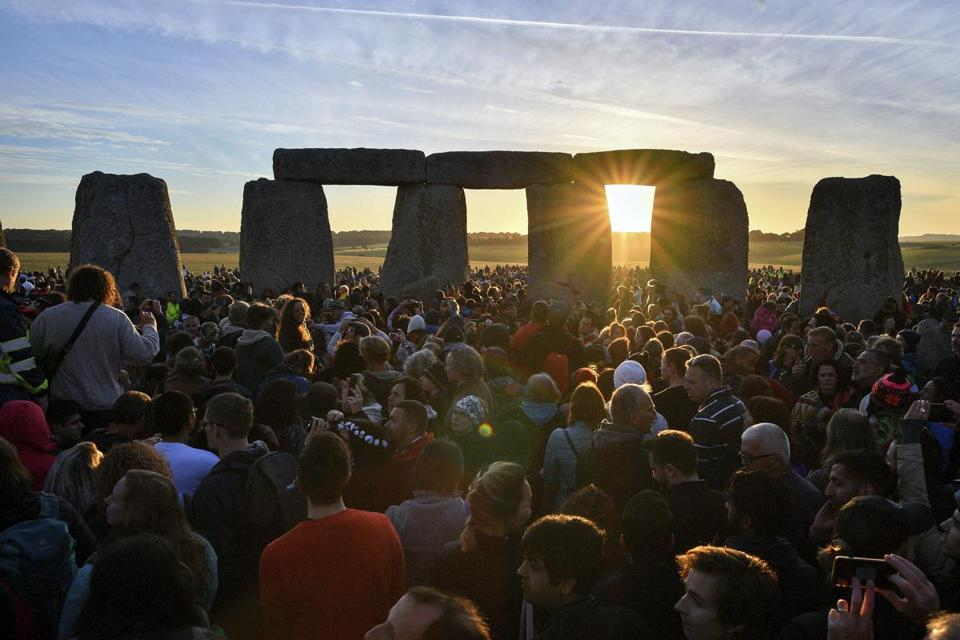 The sun rises through the stones at Stonehenge as crowds of people gather to celebrate the dawn of the longest day in the UK, in Wiltshire, England, Thursday June 21, 2018. The neolithic Wiltshire monument is built along the solstice alignment of the summer sunrise and the winter sunset. (Ben Birchall/PA via AP)