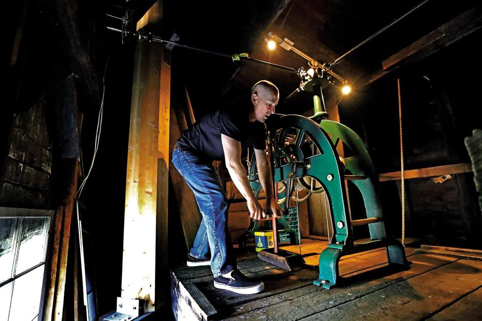Kevin Rowe has to turn the crank handle 27 times to wind the 19th-century clock in Hingham's New North Church.
