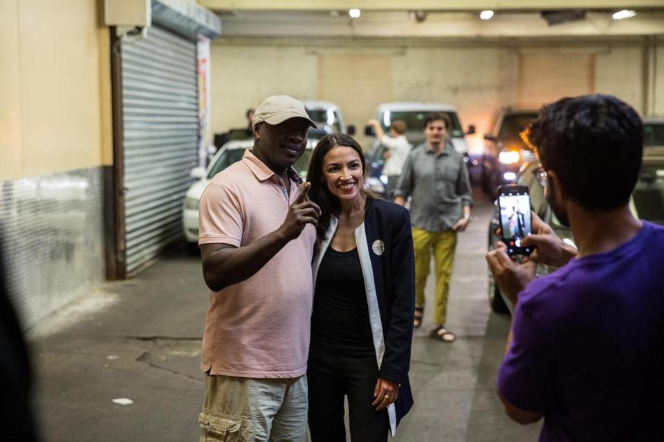 Alexandria Ocasio-Cortez posed with a supporter Tuesday. The Boston University alumna upset a high-ranking House Democrat in a primary.