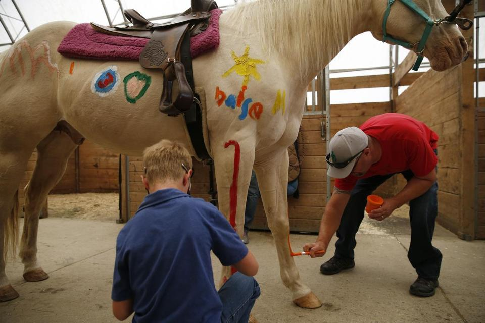 Mt. Vernon, ME--6/26/2018-- Marine Chad Brampton, of Star, Idaho who was wounded in Iraq, (R) paints a horse with his son, Lukas, 8, at Pure Country Stables. (Jessica Rinaldi/Globe Staff) Topic: 01maine Reporter: Brian MacQuarrie