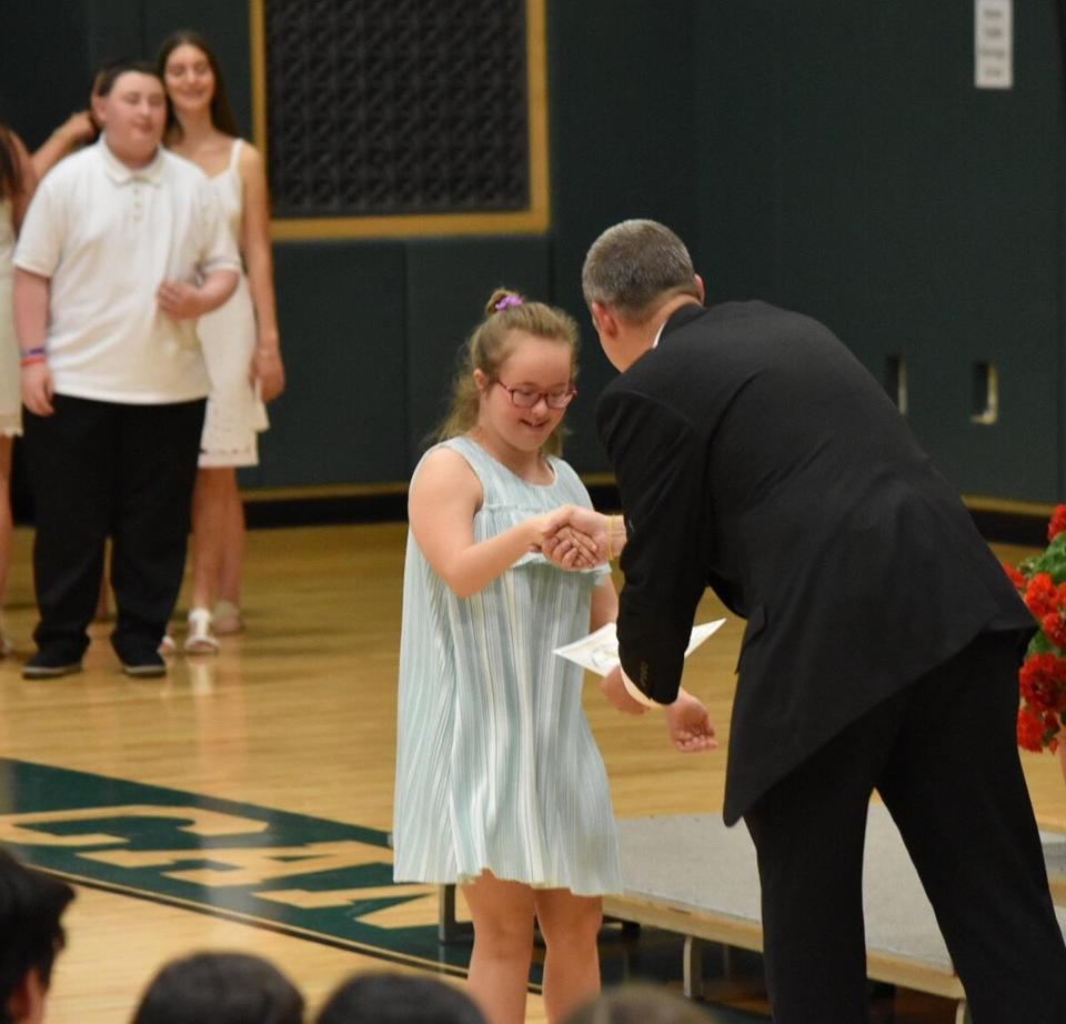01zobeckham -- Lucy Rose Falcone accepts her diploma at CantonŐs Galvin Middle School. (Scott Clyve)