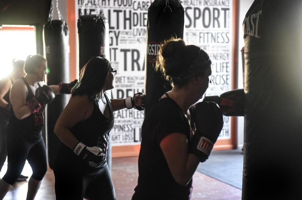 Class members punch during a Spicy Boxing class Tuesday, May 22, 2018, at We Thrive Fitness in Monticello, Minn. The high-energy workout mixes punching bag and Latin dance moves. (Dave Schwarz/St. Cloud Times via AP)
