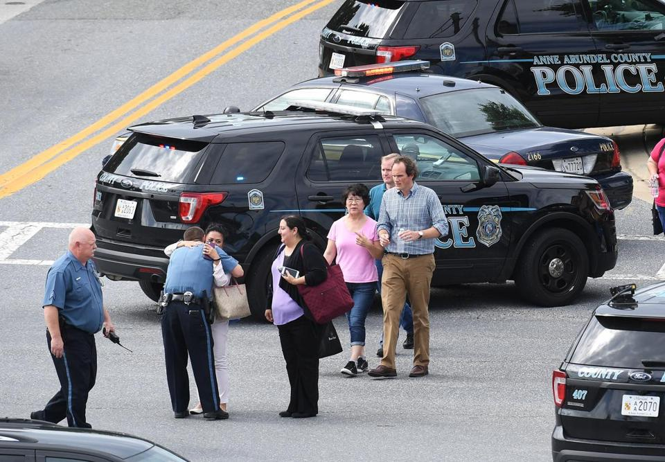 People walk from the direction of the Capital Gazette building, where five people were fatally shot Thursday in Annapolis, Maryland. MUST CREDIT: Washington Post photo by Matt McClain