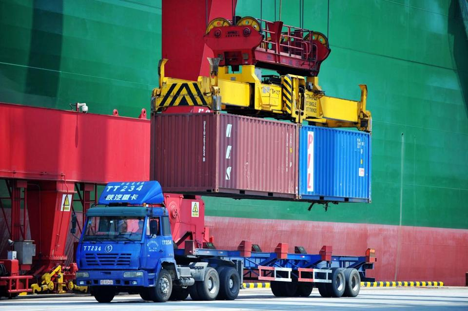 Shipping containers are transferred at a port in Qingdao in China's eastern Shandong province on Friday.