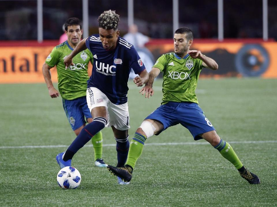 New England Revolution's Juan Agudelo, center, and Seattle Sounders's Victor Rodriguez (8) battle for the ball during the second half of an MLS soccer game in Foxborough, Mass., Saturday, July 7, 2018. (AP Photo/Michael Dwyer)