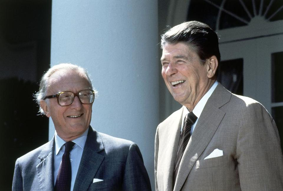 FILE- In this file photo dated Tuesday, Sept. 11, 1984, US President Ronald Reagan and NATO Secretary General Lord Carrington, left, pose for photographers in the Rose Garden prior to talks at the White House in Washington, D.C., United States. Peter Carrington, a long-serving British politician who was the last survivor of Prime Minister Winston Churchill's government, died aged 99 on Monday July 9, 2018, according to the House of Lords website. (AP Photo/Barry Thumma, FILE)