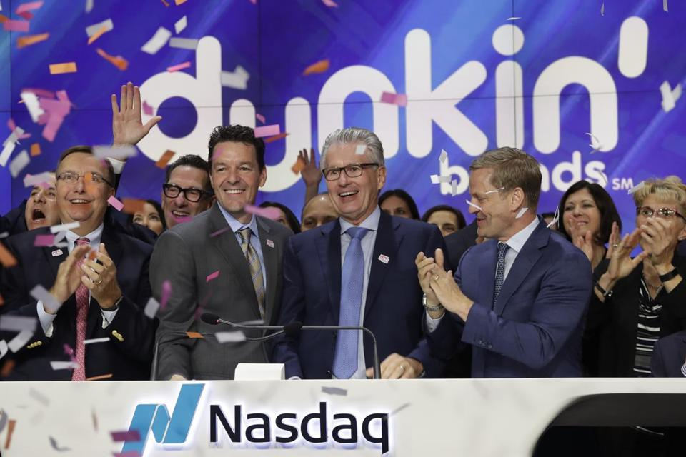 Nigel Travis, center, the retiring chairman and CEO of Dunkin' Brands, during an opening bell ceremony at Nasdaq in New York last year.