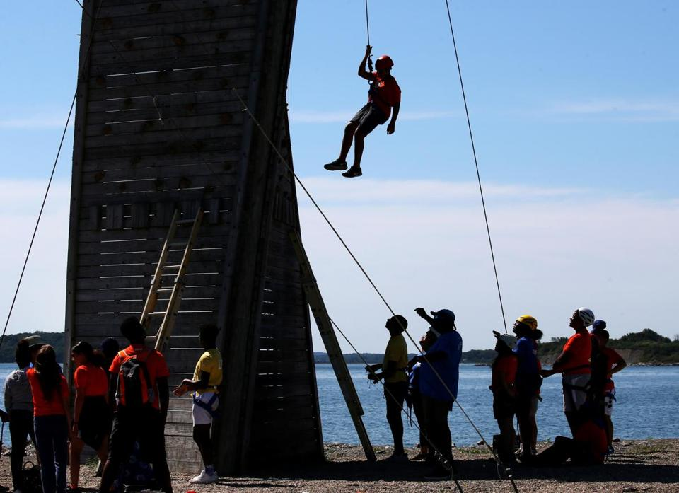 BOSTON, MA - 7/12/2018: At Camp Harbor View....... hanging off wall from rope after a climb is camper Adrian Torres (David L Ryan/Globe Staff ) SECTION: METRO TOPIC 13camppic