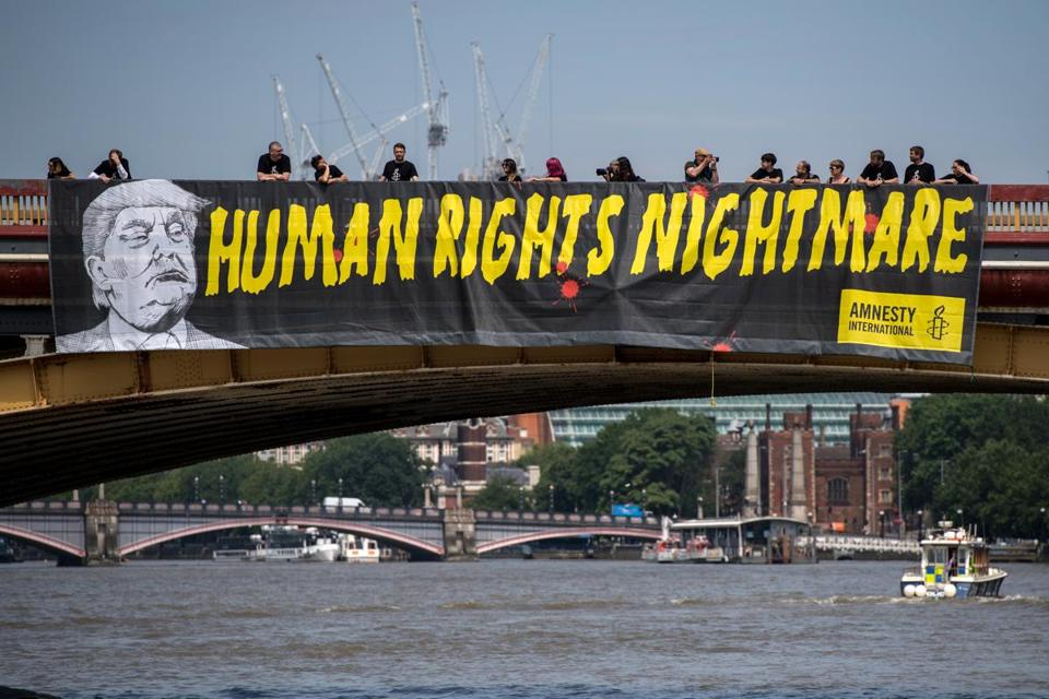 LONDON, UNITED KINGDOM - JULY 12: Human rights group Amnesty International drop a banner from Vauxhall Bridge opposite the US Embassy protesting against US President Donald Trump's visit to the United Kingdom on July 12, 2018 in London, United Kingdom. The President of the United States and First Lady, Melania Trump, have arrive in the United Kingdom for their first official visit. Whilst they are here they will have dinner at Blenheim Palace, visit Prime Minister Theresa May at Chequers and take tea with the Queen at Windsor Castle. (Photo by Chris J Ratcliffe/Getty Images)