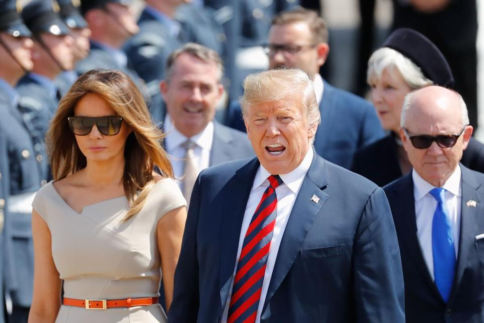 US President Donald Trump (C) and US First Lady Melania Trump (L) walk on the tarmac with US Ambassador to the United Kingdom Woody Johnson (R) as they disembark Air Force One at Stansted Airport, north of London on July 12, 2018, as he begins his first visit to the UK as US president. The four-day trip, which will include talks with Prime Minister Theresa May, tea with Queen Elizabeth II and a private weekend in Scotland, is set to be greeted by a leftist-organised mass protest in London on Friday. / AFP PHOTO / Tolga AKMENTOLGA AKMEN/AFP/Getty Images