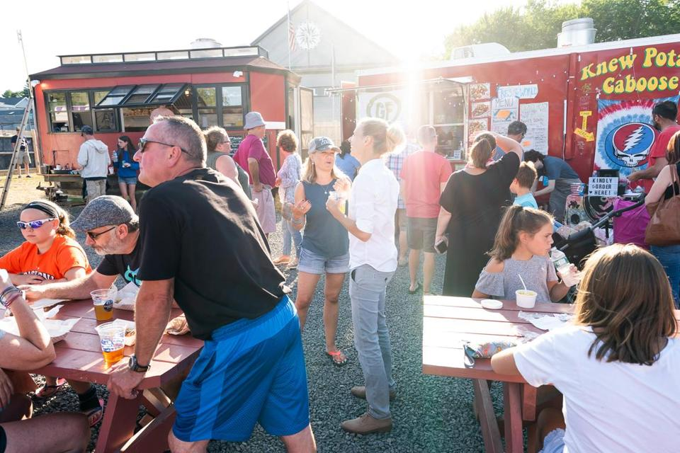The scene at Congdon's After Dark Food Truck Park includes people sitting at tables and walking among the trucks