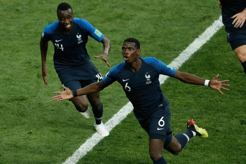 France's midfielder Paul Pogba celebrates with teammates after scoring a goal.