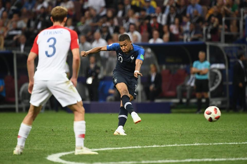 France's forward Kylian Mbappe shoots to score his team's forth goal.