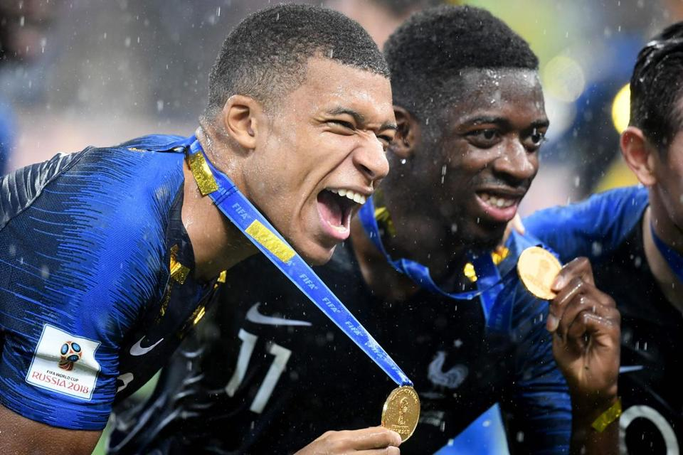 France's Kylian Mbappe (left) and Ousmane Dembele show off their gold medals.