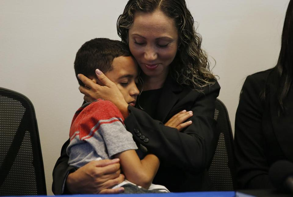 Allston, MA--7/16/2018-- An Immigrant mother who has asked to be identified by the initials W.R. cradles her 9 year-old son, A.R. during a press conference at the Brazilian Worker Center. (Jessica Rinaldi/Globe Staff) Topic: 17reunionpic Reporter: