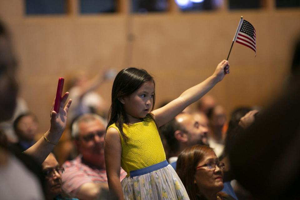 A young girl waves an American flag at the naturalization ceremony at the JFK Library and Museum on Wednesday.