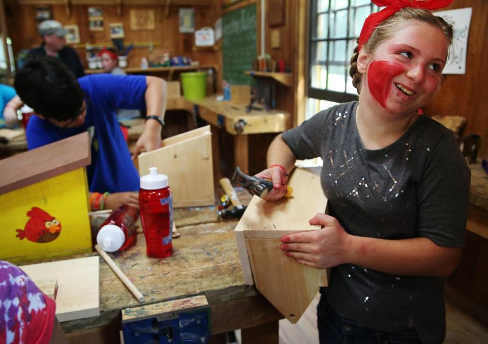 ASHFORD, CT - 07/16/2018 Isabella laughs with a counselor while making a birdhouse in the woodshop during their program activities. Created by Paul Newman in 1988, Hole in the Wall Gang Camp is dedicated to providing a week long camp experience to seriously ill children and their families. Erin Clark for the Boston Globe