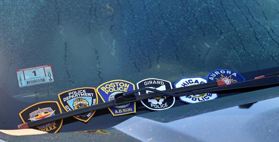 Shoulder patches were stuck under the windshield of Chesna's police vehicle at the funeral for slain Weymouth police  Sergeant Michael Chesna.