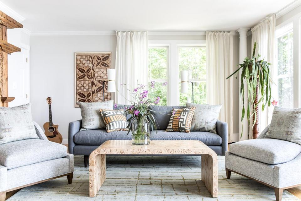 In the living room, a framed print reminiscent of African mud cloth and a burl-wood waterfall coffee table lend an earthy feel.