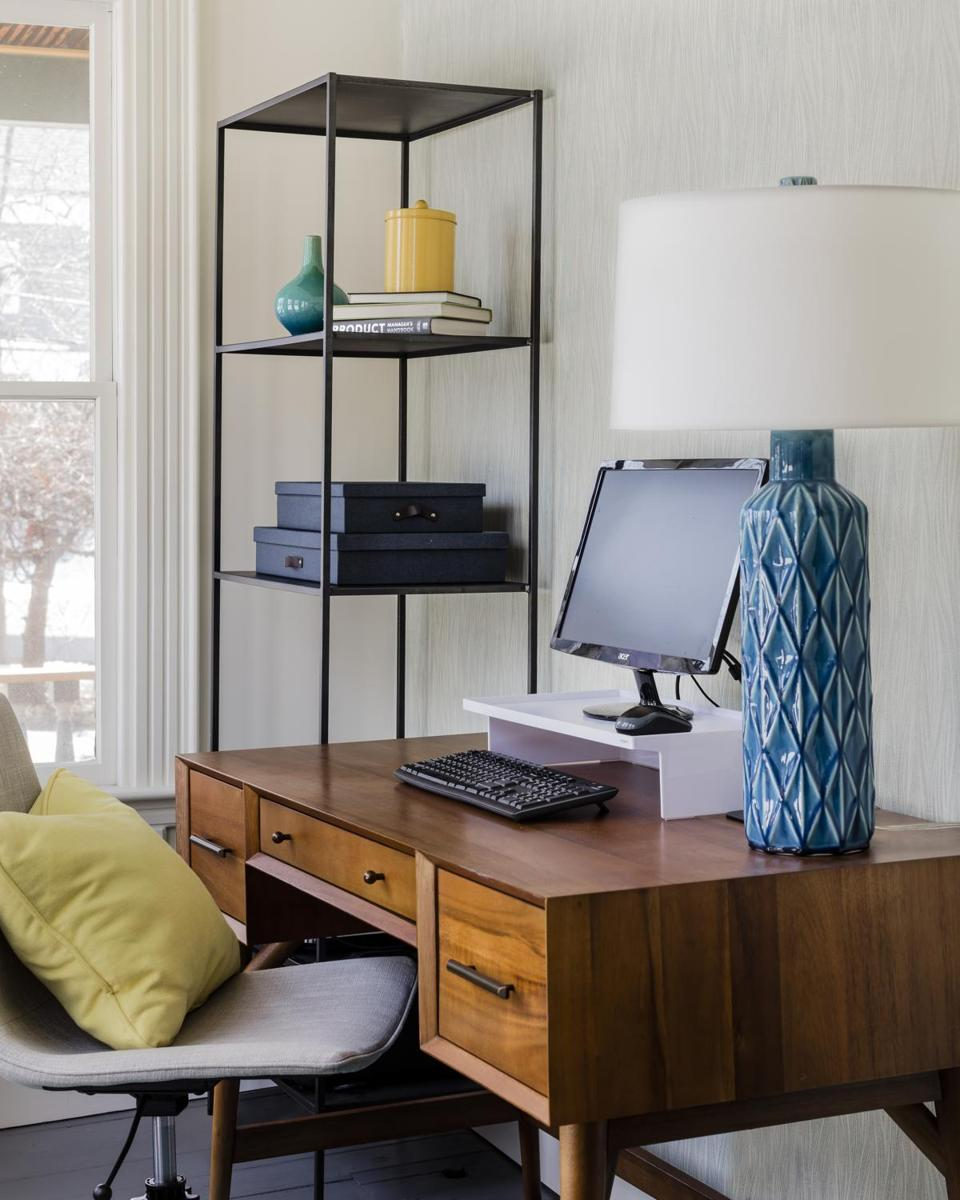 In the sunroom-turned-office (below), which is visible from the dining room, the teal-and-yellow color scheme carries through. The desk is from West Elm, and the lamp is by Arteriors Home.