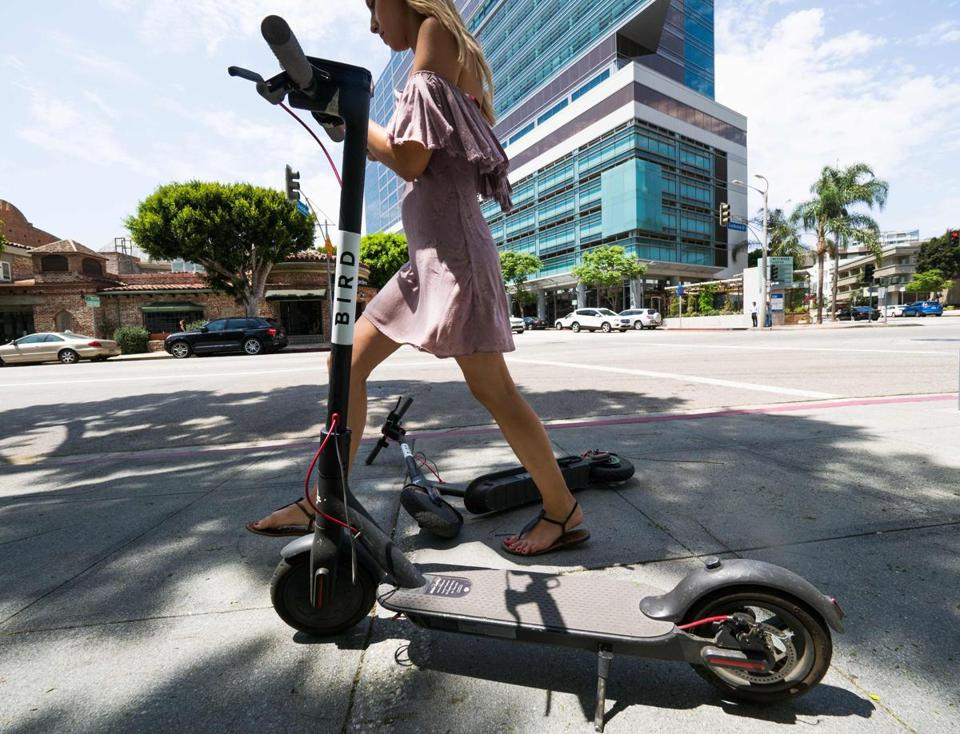 A pedestrian walks between two Bird dockless scooters in Los Angeles.