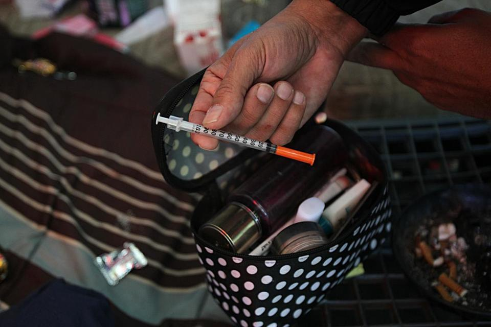 Lowell, Ma., 10/12/16, Louie Diaz finds a needle while searching through a tent for the identity of the occupant. The opioid crisis has many victims, but some of the most vulnerable are former inmates who leave prison for the streets with few tools to avoid relapse into addiction. We walk the streets of Lowell with Louie Diaz, a former prisoner and addict, who now makes the rounds daily -- to alleys, shabby tenements, and tents -- in a difficult effort to bring help to the desperate. Globe staff/ Suzanne Kreiter