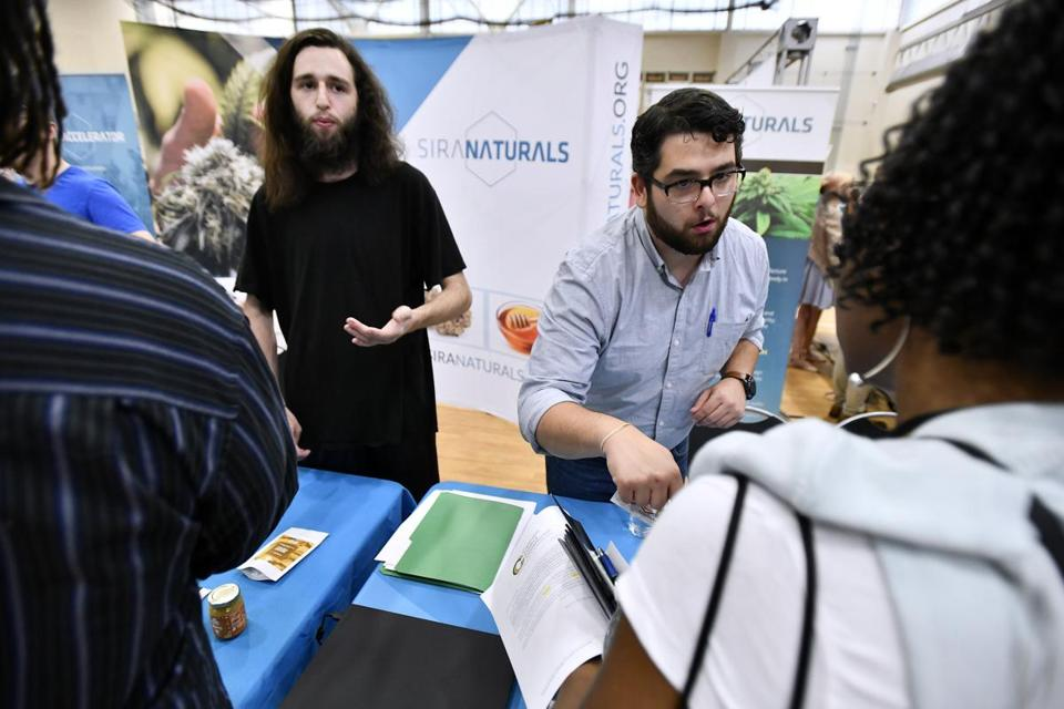 BOSTON, 7/25/2018 - From left, Processing Technician Aaron Wang and Director of Marketing Nic DiBella of Somervile and Cambridge Based marijuana product producer Siri Naturals speak with prospective employees at the cannabis industry job fair and expungement clinic at the Reggie Lewis Track and Athletic Center in Roxbury. Josh Reynolds for The Boston Globe (Metro, Desk )