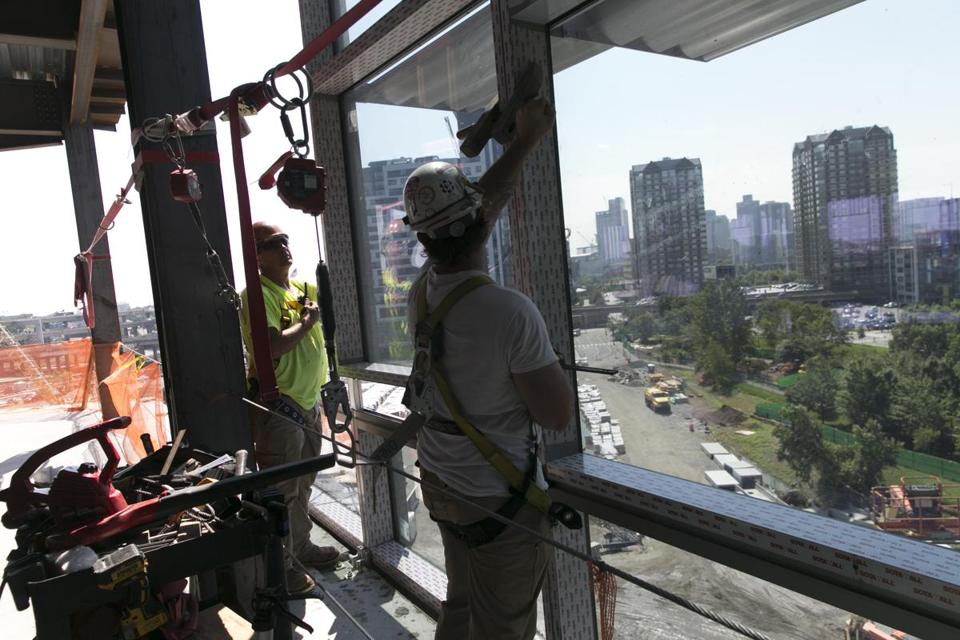 Workers installed a glass facade at a building in Cambridge Crossing, one of several projects near the Orange Line.