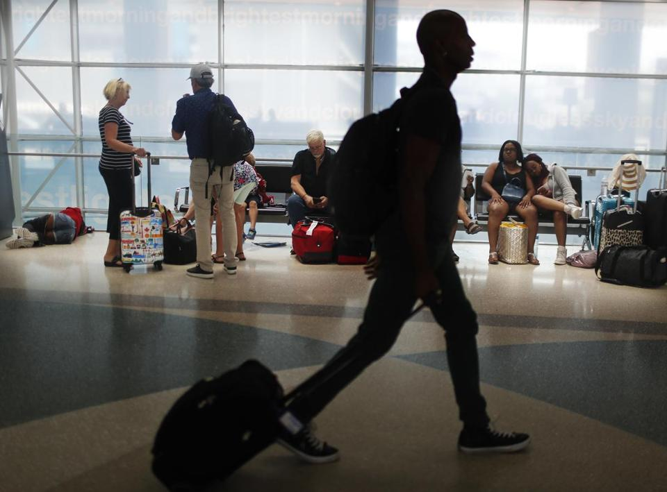 Travelers gather on benches to wait for delayed and arriving flights as others rush to their gate at the Fort LauderdaleÐHollywood International Airport on Friday, June 29, 2018, in Fort Lauderdale, Fla. The TSA projected that Friday would be its busiest day ever, with agents screening more than 2.7 million people. (AP Photo/Brynn Anderson)
