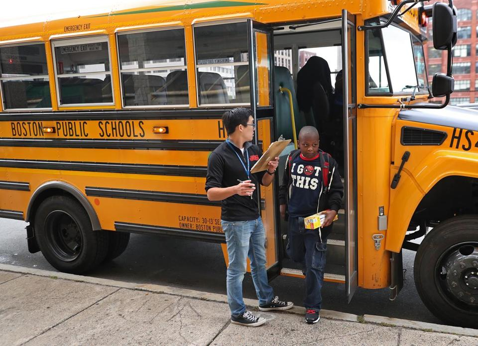 BBOSTON, MA - 9/07/2017: A Boston Public School employee monitors the arrival of a bus as a student exits the bus. Busses arrive in the morning at the Quincy School, Chinatown on the first day of school for Boston that is today with the focus on whether the new bus routes actually work. (David L Ryan/Globe Staff ) SECTION: METRO TOPIC