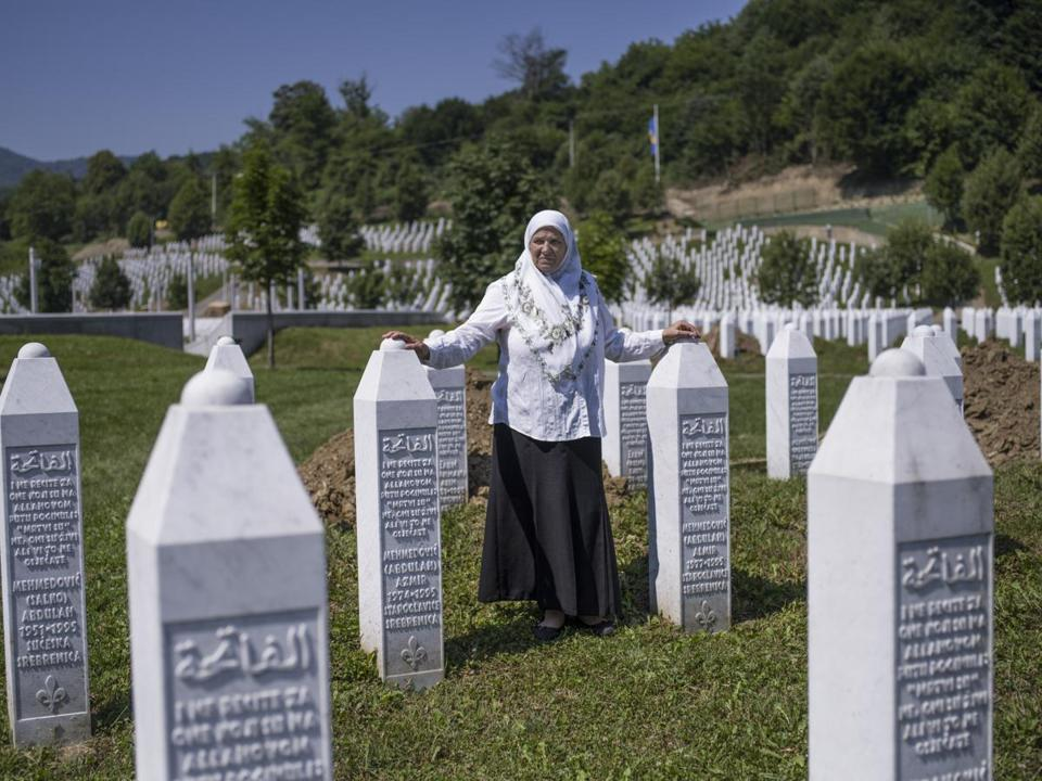 Mrs. Mehmedovic, next to the gravestones of her two sons at a cemetery for victims of the massacre at Srebrenica.