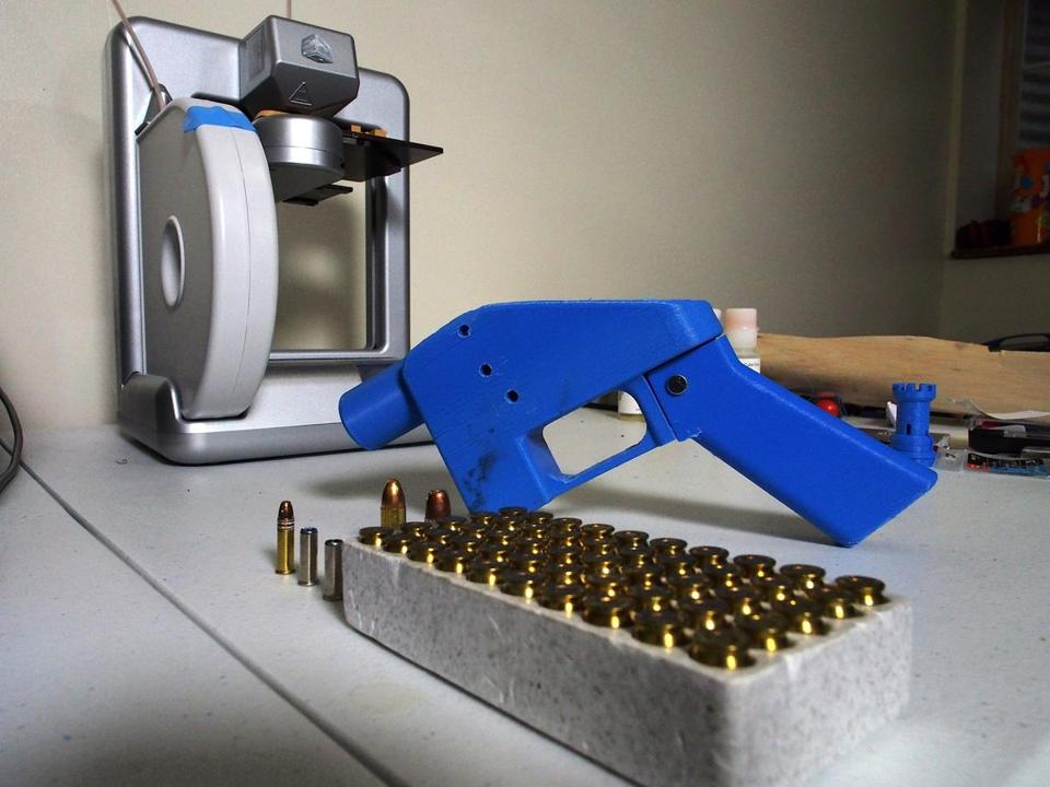 "A ""Liberator"" pistol pictured next to the 3-D printer on which its components were made."