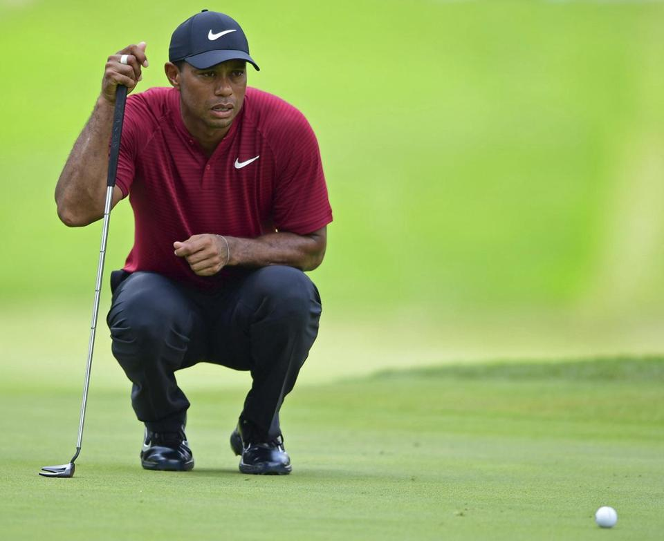 Tiger Woods examines the green on the fifth hole during the final round of the Bridgestone Invitational golf tournament at Firestone Country Club, Sunday, Aug. 5, 2018, in Akron, Ohio. (AP Photo/David Dermer)