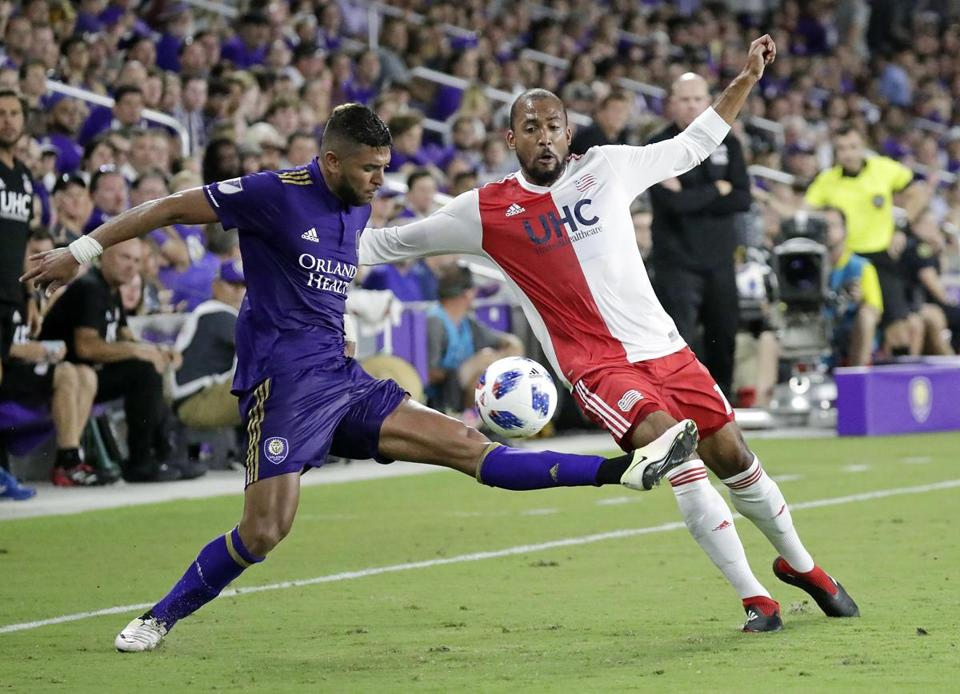 Orlando City's Amro Tarek, left, tries to clear the ball from New England Revolution's Teal Bunbury during the second half of an MLS soccer match, Saturday, Aug. 4, 2018, in Orlando, Fla. (AP Photo/John Raoux)