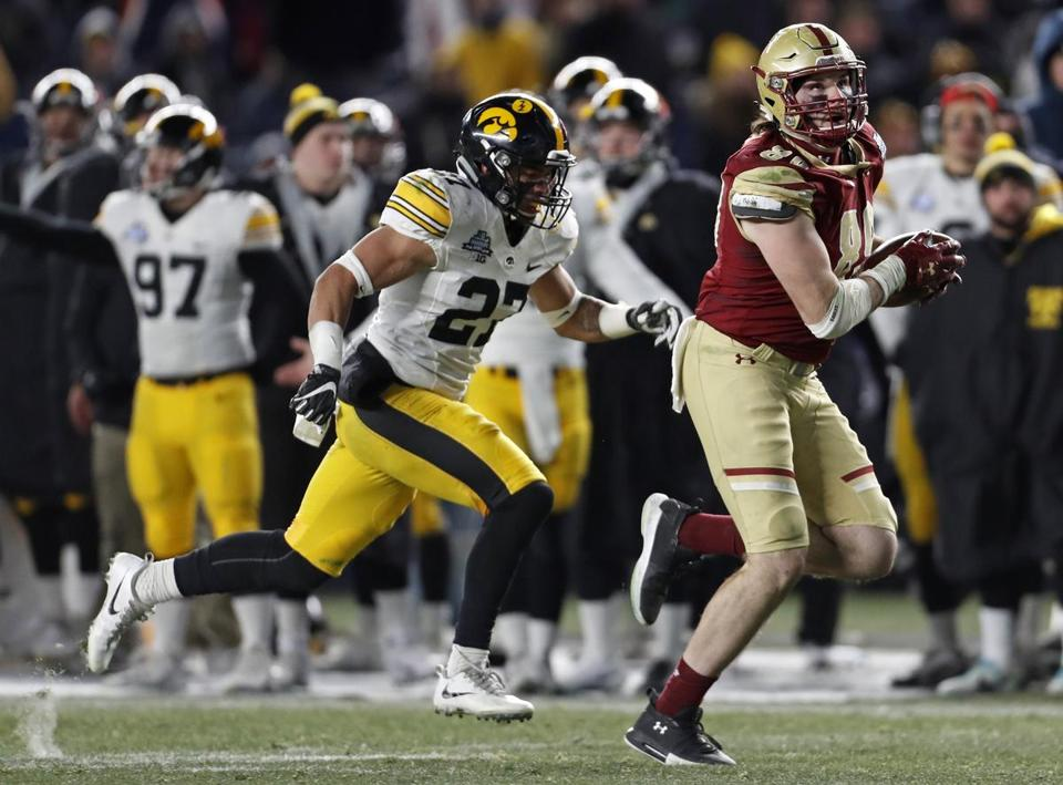 NEW YORK, NY - DECEMBER 27: Tommy Sweeney #89 of the Boston College Eagles is chased by Amani Hooker #27 of the Iowa Hawkeyes during the second half of the New Era Pinstripe Bowl at Yankee Stadium on December 27, 2017 in the Bronx borough of New York City. The Iowa Hawkeyes won 27-20. (Photo by Adam Hunger/Getty Images)