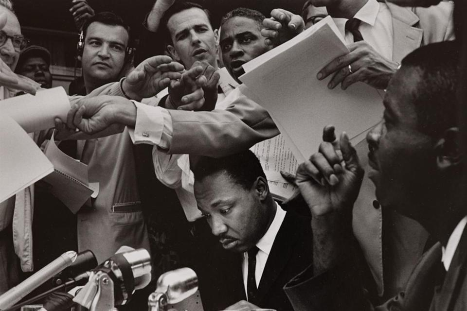 "Bruce Davidson's photograph of Martin Luther King Jr. at a 1962 press conference, in Birmingham, Ala. Below: Brad Kayal's ""Job Creator"" (left) and Dave Cole's ""American Flag (Toy Soldiers #12)."""