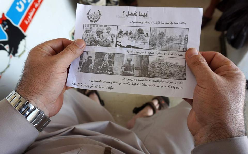 A Syrian man held a leaflet stamped with the government forces' seal and dropped by helicopters flying over the Syrian city of Saraqib, southwest of Aleppo.