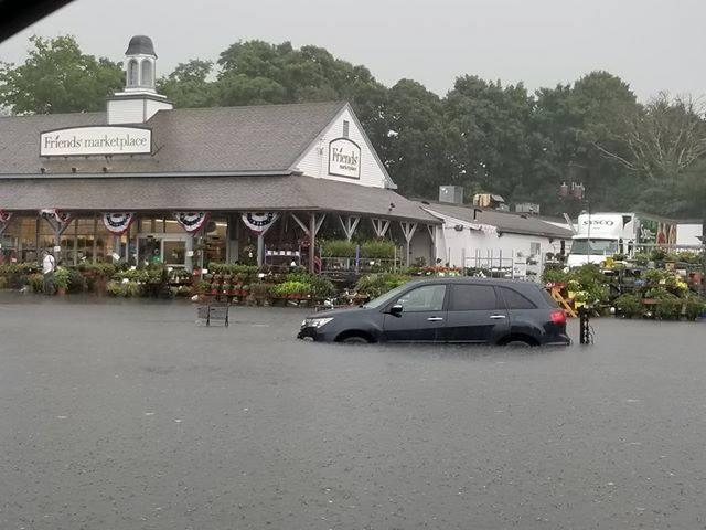 Flooding due to heavy rain in the parking lot of Friends Marketplace in Orleans Thursday.
