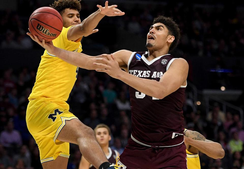 LOS ANGELES, CA - MARCH 22: Tyler Davis #34 of the Texas A&M Aggies goes up for a shot against Isaiah Livers #4 of the Michigan Wolverines in the second half in the 2018 NCAA Men's Basketball Tournament West Regional at Staples Center on March 22, 2018 in Los Angeles, California. (Photo by Harry How/Getty Images)