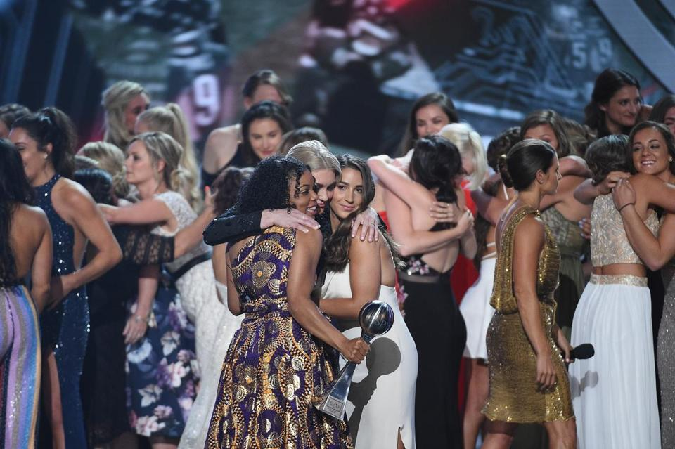 Aly Raisman, Sarah Klein, and Tiffany Thomas Lopez hug on stage at the ESPYs after receiving the Arthur Ashe Award for Courage alongside more than 100 other survivors.